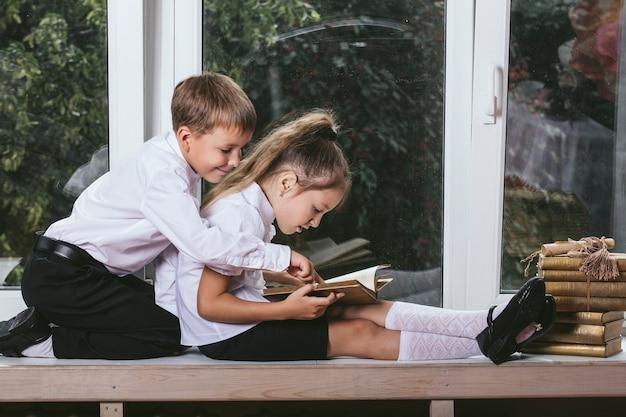 행복 한 소년과 소녀 배경에 책을 읽고 창턱에 앉아 프리미엄 사진