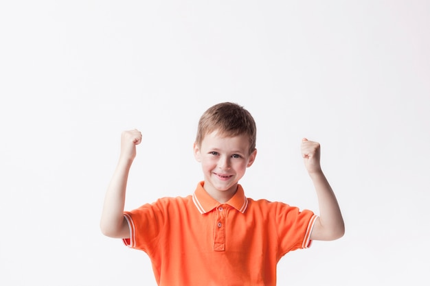 Happy boy clenching fist making yes gesture on white wall Free Photo