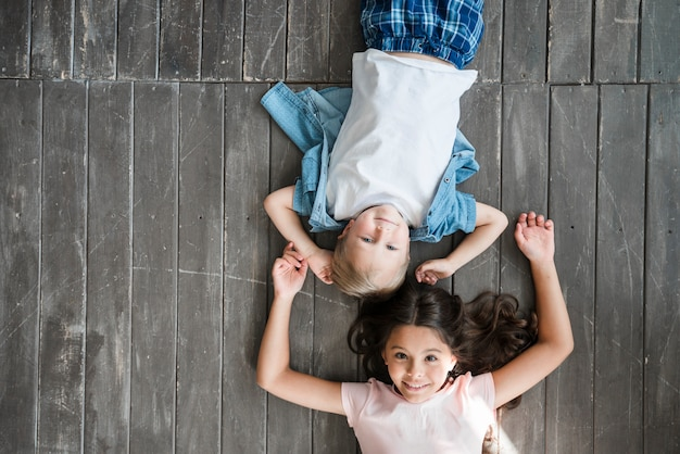 Happy boy and girl lying on hardwood floor Free Photo