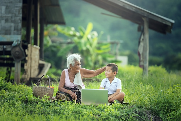 Happy boy and grandmother using a laptop outdoors Premium Photo
