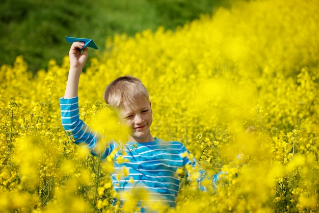 Happy boy holds in hand blue paper airplane on bright sunny day in the yellow field fowers Premium Photo