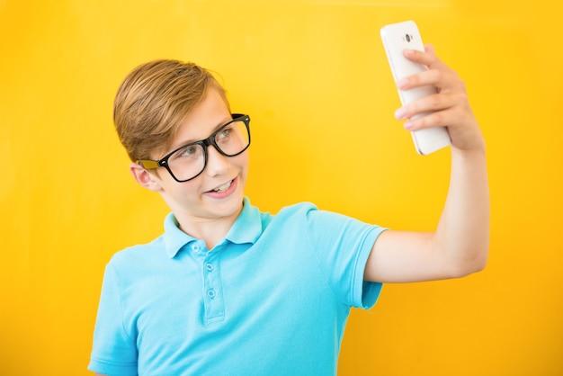 Счастливый мальчик делает селфи на желтом фоне Premium Фотографии
