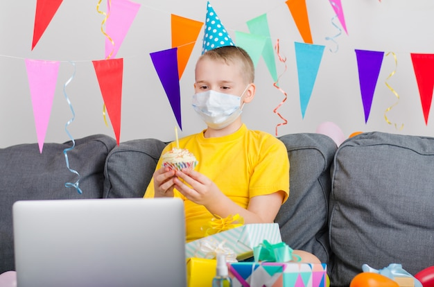 Happy boy in medicine face mask celebrates birthday by video call to laptop Premium Photo