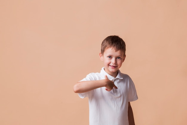 Happy boy pointing finger at himself standing near beige wall Free Photo