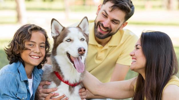 Счастливый мальчик позирует в парке с собакой и родителями Бесплатные Фотографии