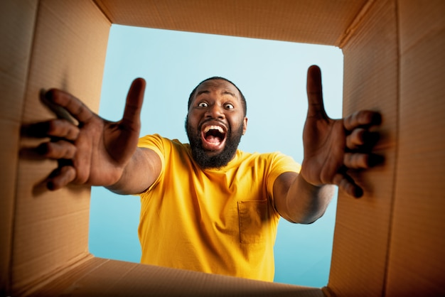 Happy boy receives a package from online shop order. happy and surprised expression Premium Photo