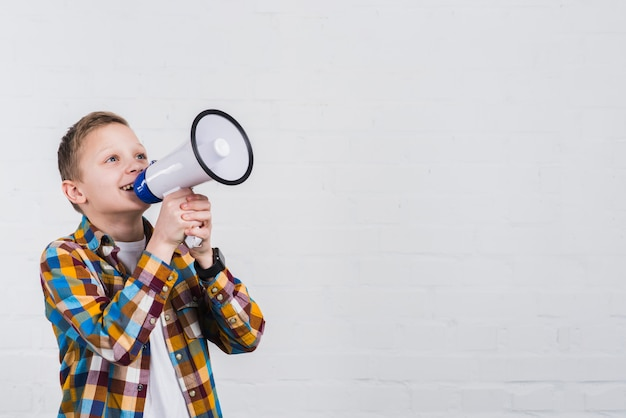 Happy boy shouting through megaphone standing against white wall Free Photo