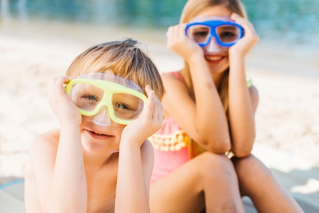 Happy boy and smiling woman in goggles sitting on sand shore Free Photo