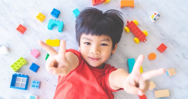 Happy boy surrounded by colorful toy blocks top view v shape hand for victory Premium Photo