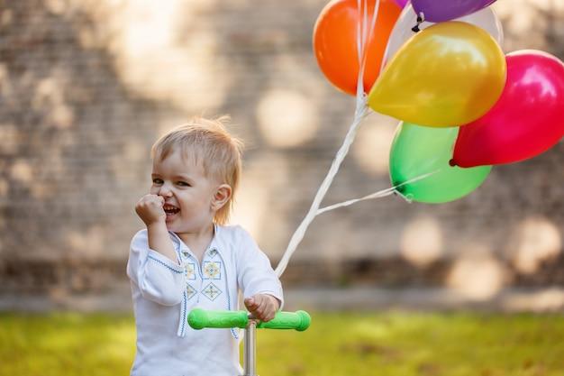 Happy boy with colorful balloon. Premium Photo