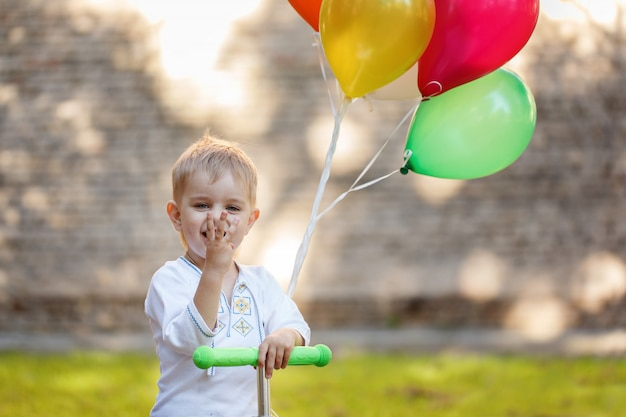 Happy boy with colorful balloon. Premium Photo