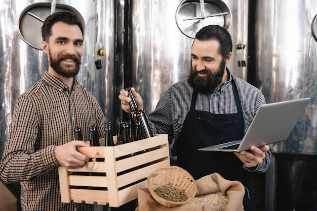Happy brewers inspecting beer bottles at factory. Premium Photo