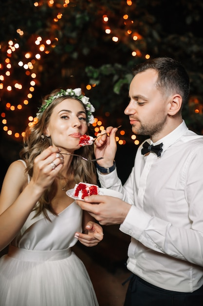 Happy bride and groom cut the wedding cake in the front garland light decoration. Premium Photo