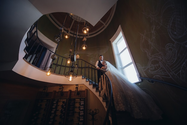Happy bride and groom kissing and hugging on a spiral staircase. portrait of loving newlyweds in a beautiful interior. wedding day. smiling just married couple Premium Photo