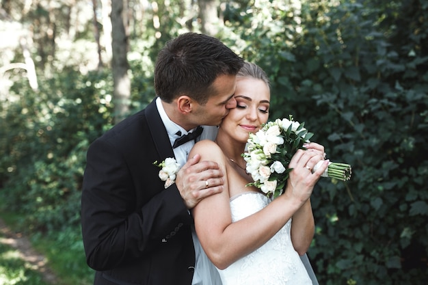 Happy bride with her wedding bouquet and her husband Free Photo