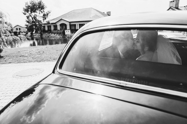 Happy brides are kissing in the car Free Photo