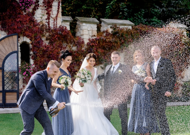 Happy bridesmaids, best men and wedding couple is celebrating wedding day outdoors with pouring out champagne Free Photo