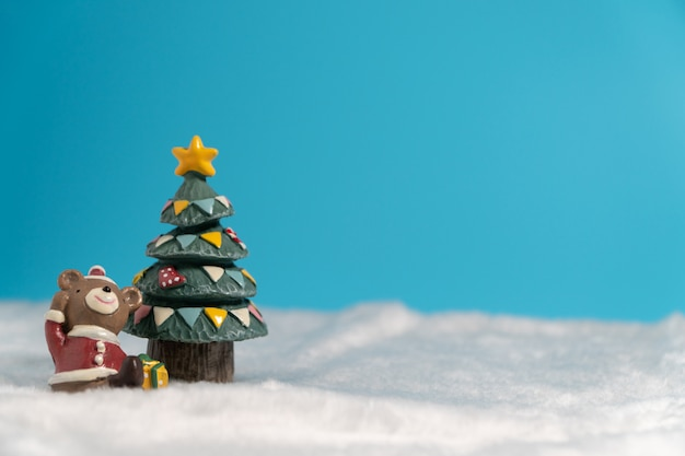 Happy brown bear wearing santa dress with gifts box siting on the snow near christmas tree. Premium Photo