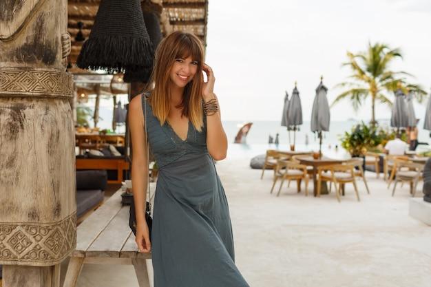 アジアンスタイルのスタイリッシュなビーチレストランでポーズをとってセクシーなドレスで幸せなブルネットの女性。 無料写真
