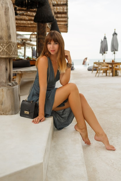 Happy brunette female in sexy dress posing in stylish  beach restaurant in  \ bali  style.  full lenght. Free Photo