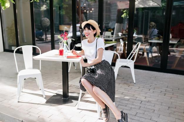黒いスカートと白いシャツを着た幸せなブルネットの少女が屋外カフェに座って、良い気分で街の景色を楽しんでいます 無料写真