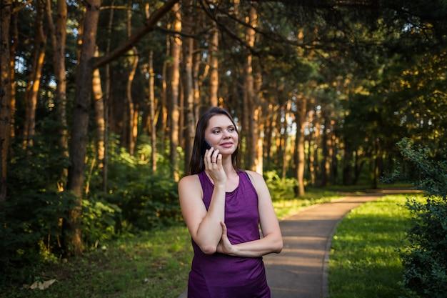Счастливая брюнетка девушка разговаривает по телефону в парке на закате Premium Фотографии