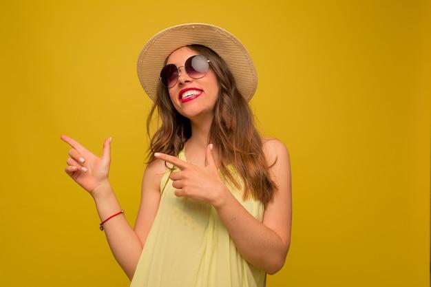 黄色のドレスと帽子の幸せなブルネットの女性が見上げる、指を指して、黄色の壁に心から笑顔 無料写真