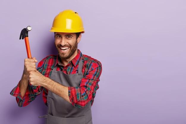 幸せなビルダーは建設用ヘルメットを着用し、ハンマーで修理します 無料写真