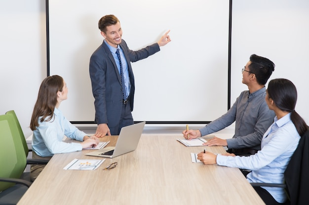 Happy business coach consulting team in boardroom Free Photo