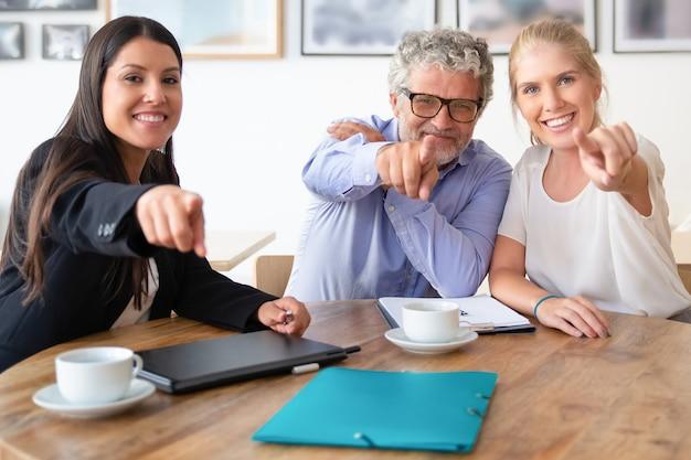 Счастливые коллеги по бизнесу или партнеры позируют и указывают на камеру, сидя за столом с кофейными чашками и документами Бесплатные Фотографии