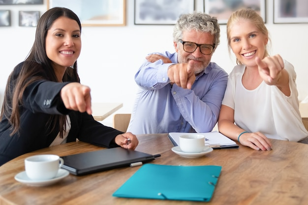 Happy business colleagues or partners posing and pointing at camera while sitting at table with coffee cups and documents Free Photo