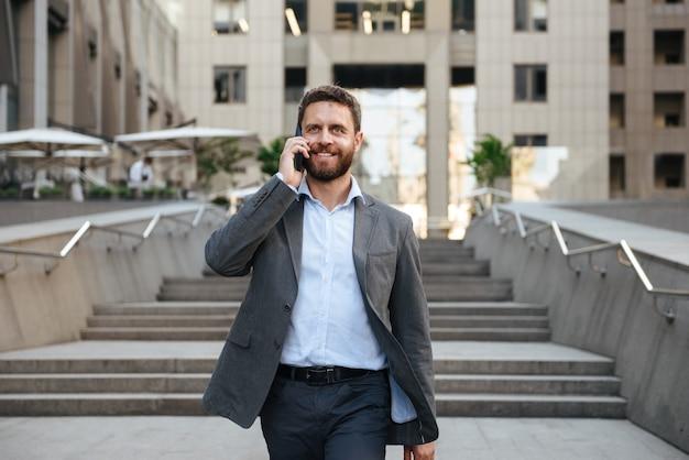 モダンなビジネスセンターの外の階段を降りながら携帯電話で話す灰色のスーツで幸せなビジネスの男性 Premium写真