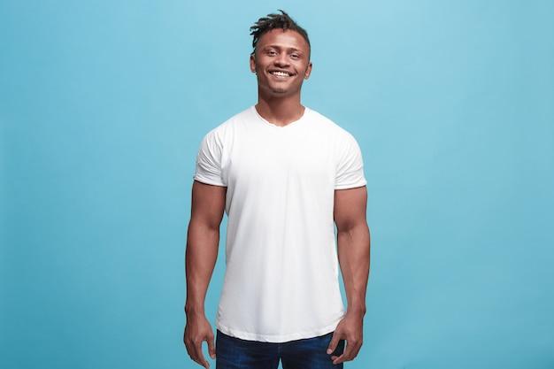 Счастливый бизнесмен стоя и усмехаясь изолированный на голубой студии. Бесплатные Фотографии