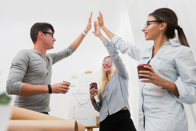 Happy business partners raising hands Free Photo