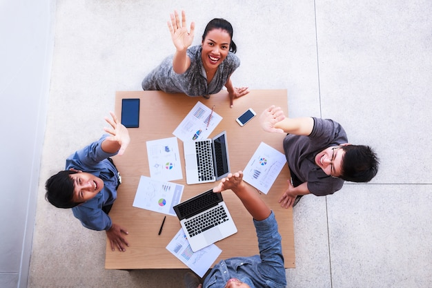 Happy business people celebrate over table in meeting at mobile office Premium Photo