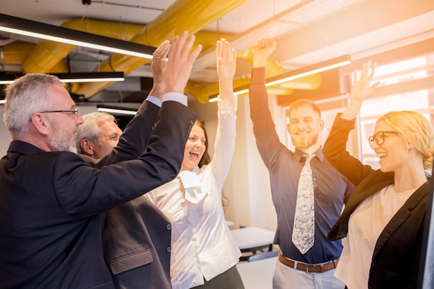 Happy business people celebrating their success in the office Free Photo