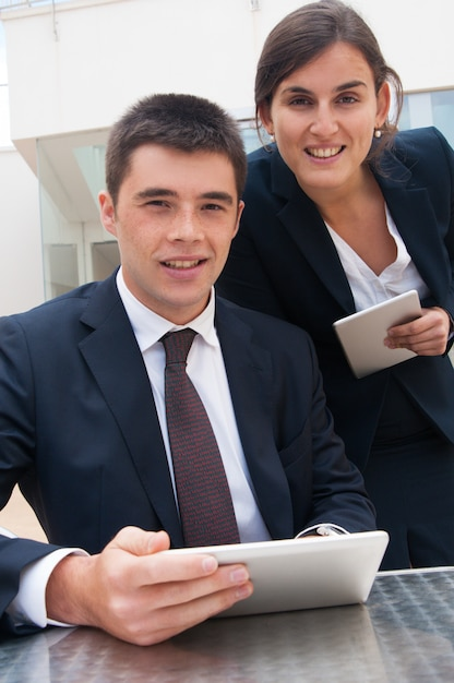 Happy business people posing at camera and holding tablets Free Photo