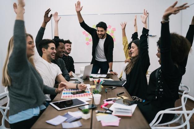 사무실에서 제기 손으로 축하 행복 비즈니스 팀. 성공과 승리의 개념. 무료 사진