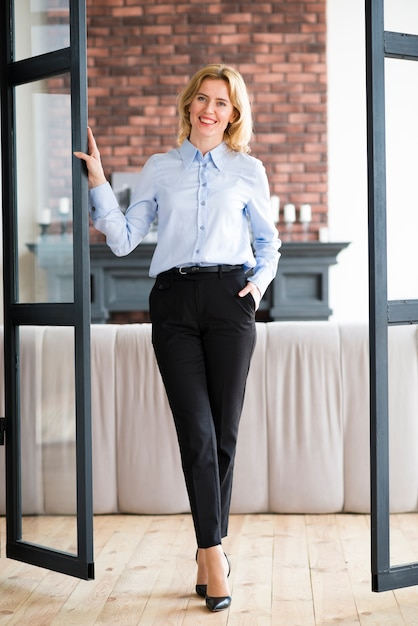 Happy business woman holding hand in pocket Free Photo