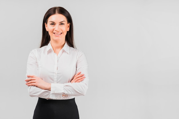Happy business woman standing with crossed arms Free Photo