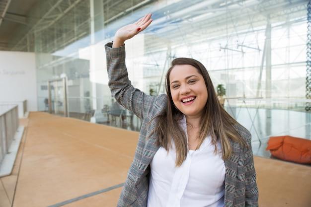 Happy business woman waving with hand outdoors Free Photo