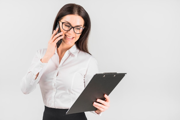 Happy business woman with clipboard talking by phone Free Photo