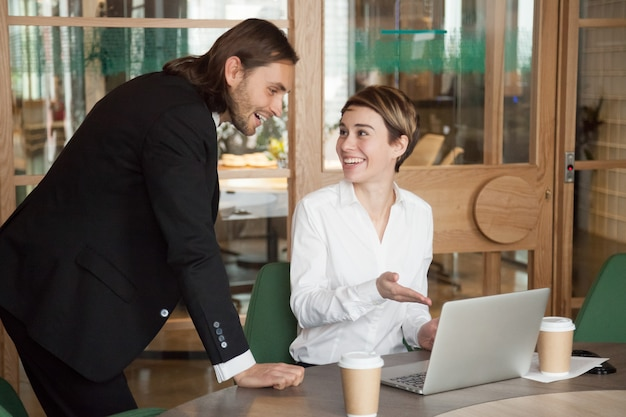 Happy businessman and businesswoman discussing good news online on laptop Free Photo