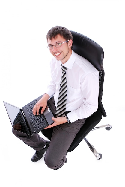 Happy businessman on chair with laptop Free Photo