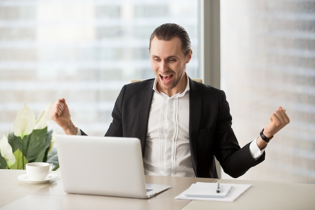 Happy businessman excited because of success Free Photo