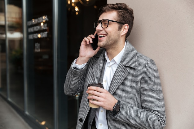Happy businessman in eyeglasses and coat talking by smartphone Free Photo