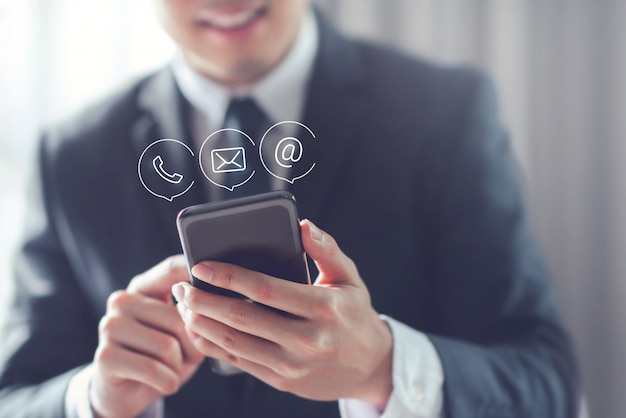 Happy businessman holding mobile smartphone with ( mail,phone,email ) icon. Premium Photo