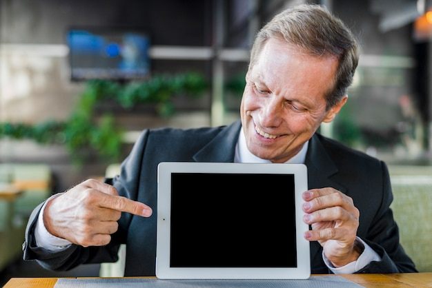 Happy businessman pointing at blank screen of digital tablet Free Photo