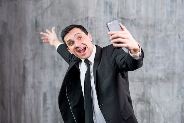 Happy businessman raising hand and taking selfie Free Photo