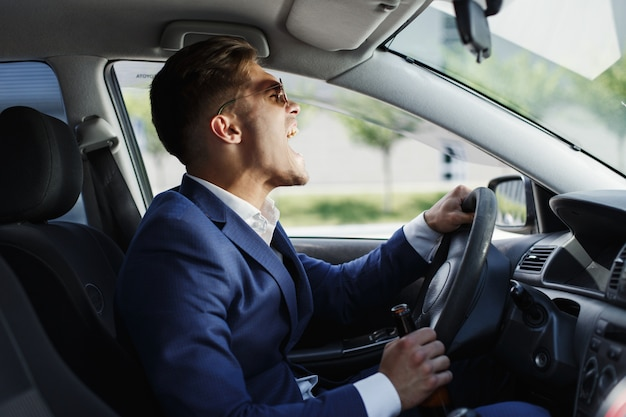 Happy businessman sits shows his emotions sitting at the steering wheel inside the car Free Photo